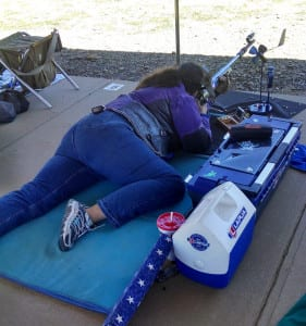 Nancy Tompkins shooting.  Smallbore shooters use personal windmills to help determine wind speed and direction.